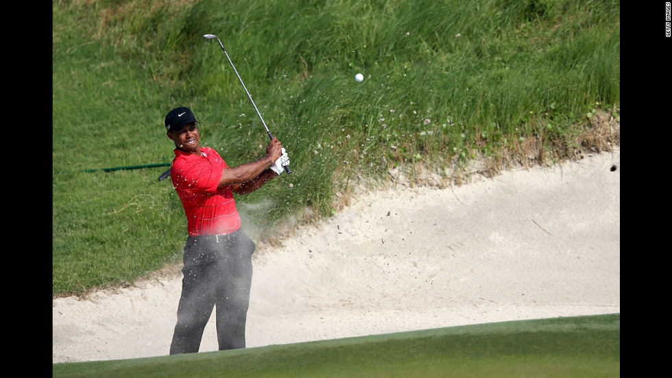 Woods tries to reach the green from a bunker on the 17th hole.