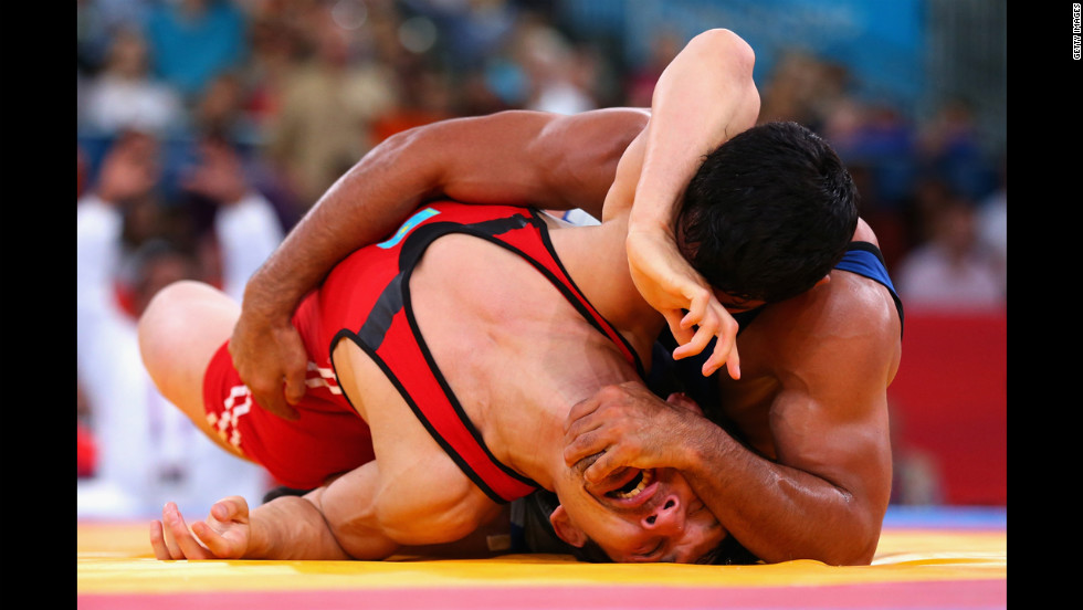 Sushil Kumar, in blue, of India battles with Akzhurek Tanatarov of Kazakhstan during the men's freestyle wrestling 66-kilogram semifinal match.