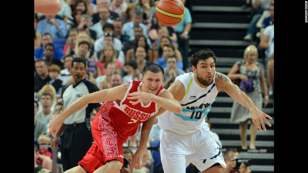 Argentine guard Carlos Delfino, right, challenges Russia's Vitaliy Fridzon for the ball during the men's bronze medal basketball game.
