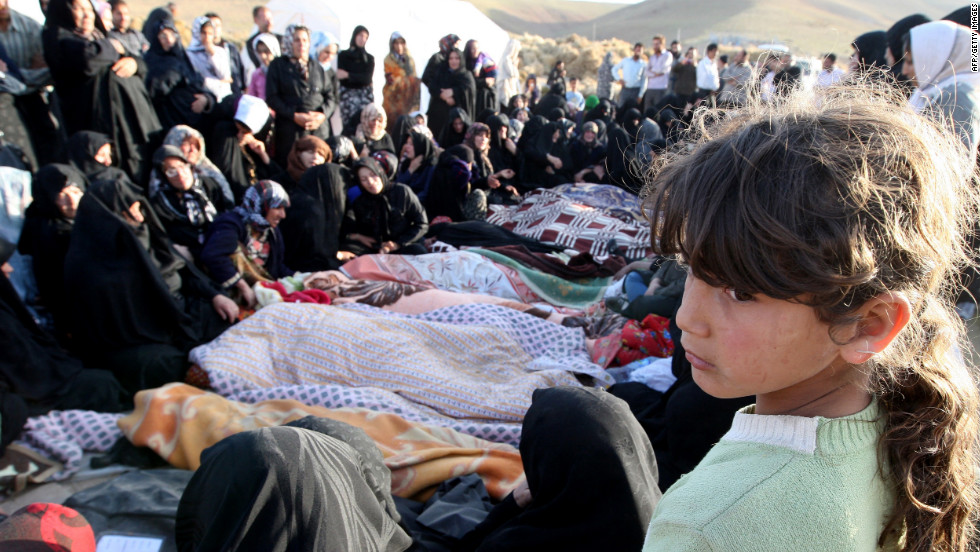 Iranians mourn over the covered bodies of loved ones in the village of Baje-Baj, Iran, on Sunday, August 12.