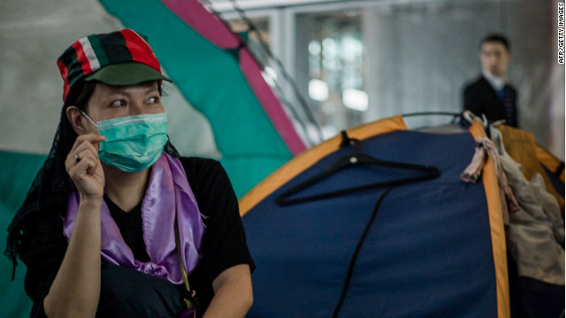 A woman sits at a protesters' camp outside the HSBC bank headquarters in Hong Kong on August 13, 2012.