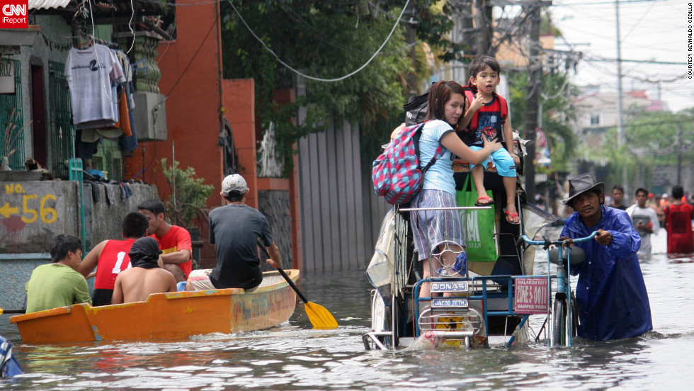 "iReporter Reynaldo Cedilla captured this image of the heavy flooding in Manila, Philippines. ""Underpasses were not passable to any type of vehicles due to the high water level. In the streets there were waist and knee deep floodwaters. ... Stranded locals tried to wade through it despite the danger,"" he said."