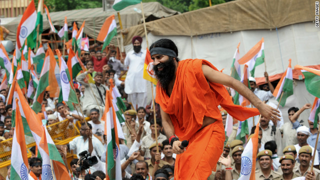 Indian yoga guru Baba Ramdev climbs on the roof of a car to address his followers in New Delhi on Tuesday.
