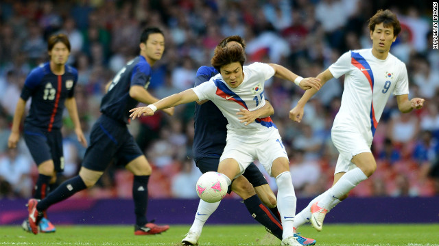 South Korean player Park Jongwoo, centre, fights for the ball with a Japanese player during the bronze medal football match on Friday.