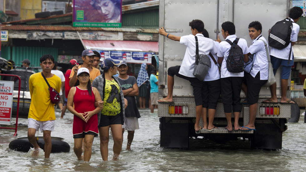 People walk along a flooded street as more rain falls in the flooded region on Tuesday, August 14,  in Bulacan.