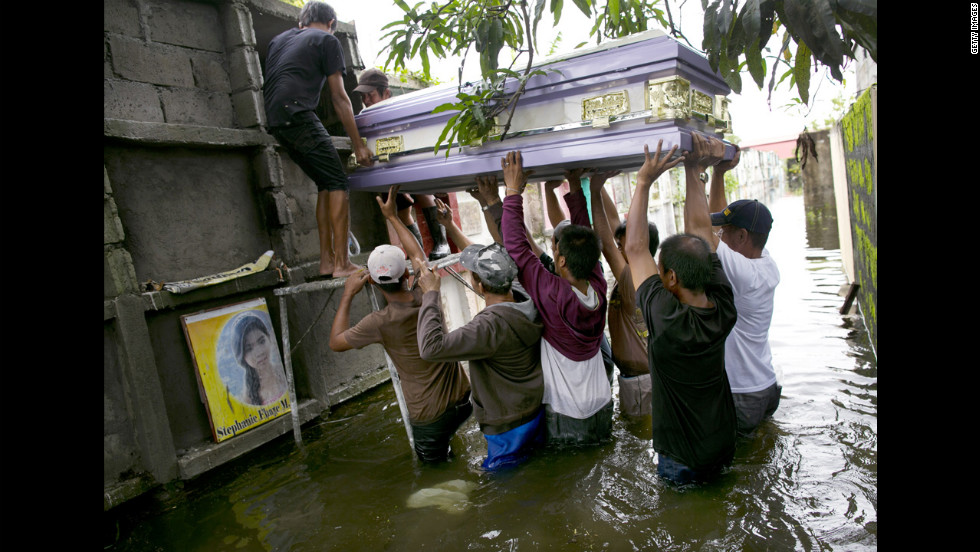 Locals lift the casket of Nelida Gregorio, 89, who died of a heart attack, into a grave site in a flooded cemetery.