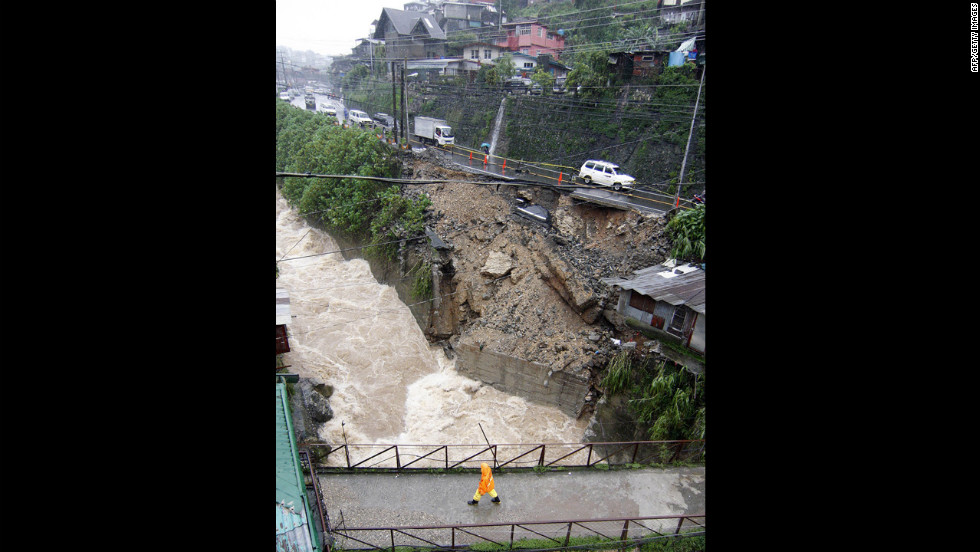 Vehicles traverse a road eroded by heavy rains along the national highway in Trinidad, Benguet province, north of Manila. Two people were killed as another tropical storm swept across the Philippines on August 15, triggering landslides in the mountainous north and dumping more heavy rain on the flood-battered capital.