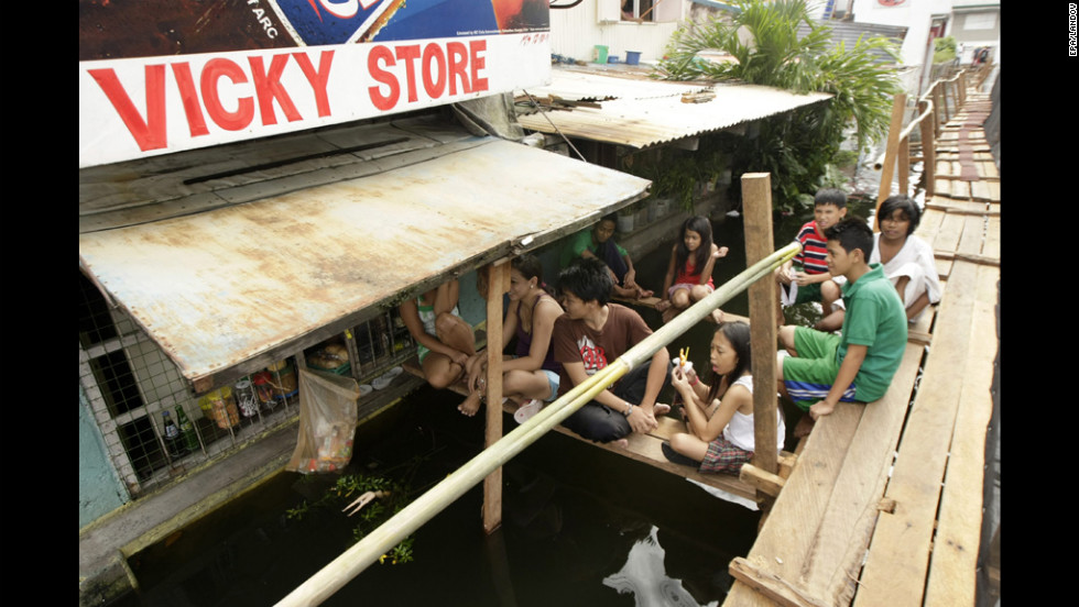 Filipinos rest on a footbridge above the flooded road.