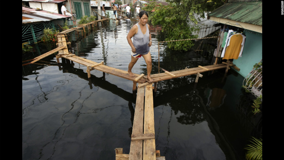 Filipino Nelia Lasona walks along a footbridge.