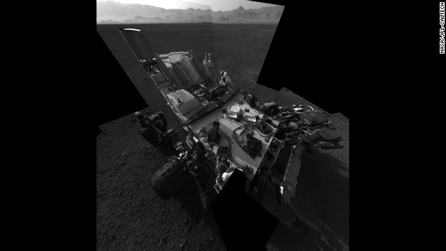 An updated self portrait of the Mars rover Curiosity, showing more of the rover's deck..  This image is a mosiac compiled from images taken from the navigation camera.  The wall of Gale crater, the rover's landing site, can be seen at the top of the image.