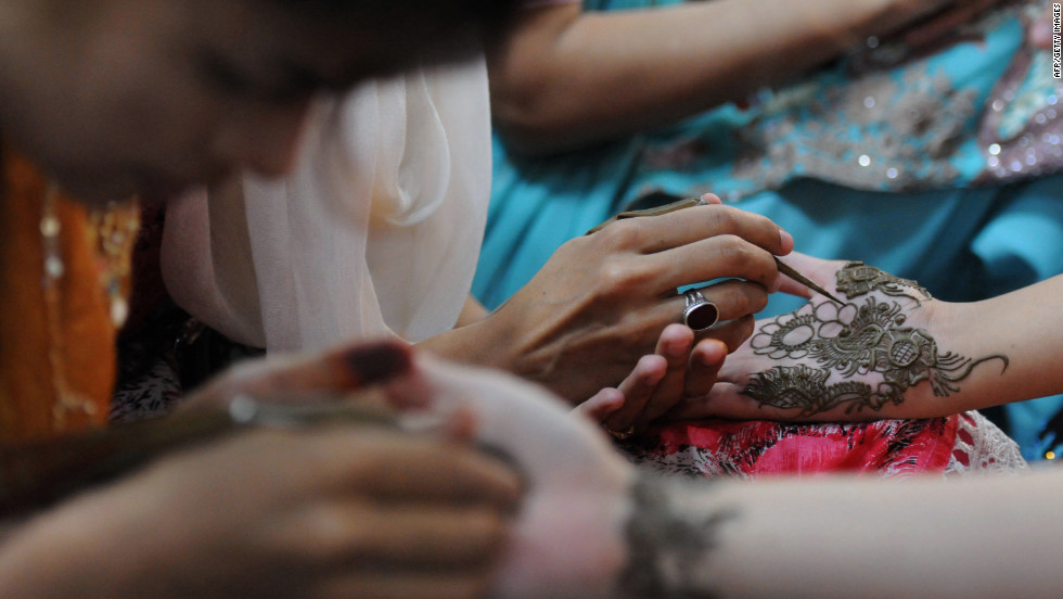 Beauticians apply traditional henna designs to the hands of customers ahead of the Muslim festivities of Eid al-Fitr in Karachi.