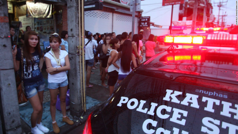 "Club goers stand in the street as police attend the scene of the fire. Eleven others were injured when flames engulfed the Tiger Bar in Patong.Photo courtesy of <a href=""http://phuketwan.com/"" target=""_blank"">Phuketwan.com</a>"