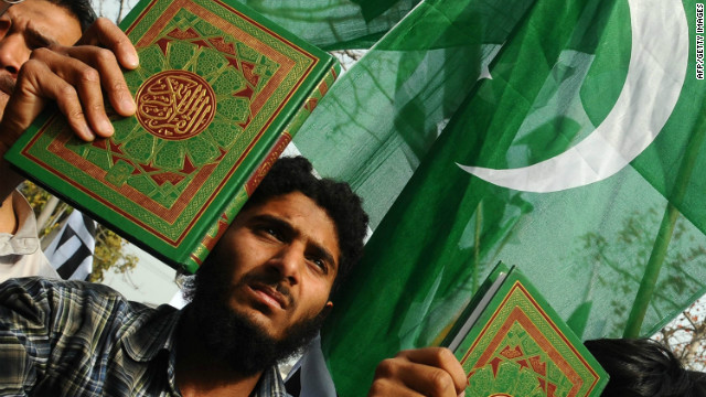 Deaf Pakistani men carry the Koran and placards during a protest in Lahore on March 18, 2012.