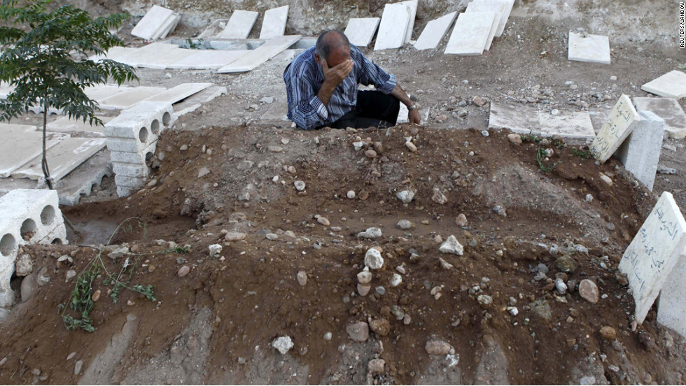A man cries near the graves of his two children killed during a recent Syrian Air Force air strike in Azaz on August 20.