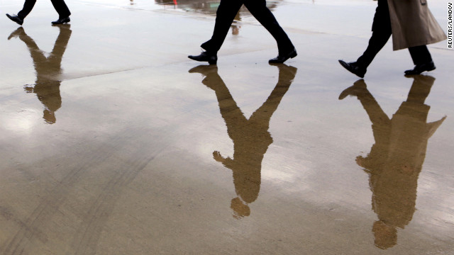 U.S. President Barack Obama (C) is reflected in a puddle as he walks from Air Force One surrounded by his security detail in Columbus, Ohio August 21, 2012.  Obama is on a two-day campaign trip to Ohio, Nevada and New York.