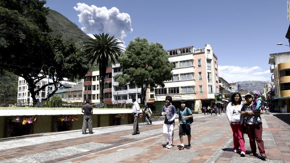 Banos residents walk through the main square of town Tuesday as the nearby Tungurahua volcano spews ashes.