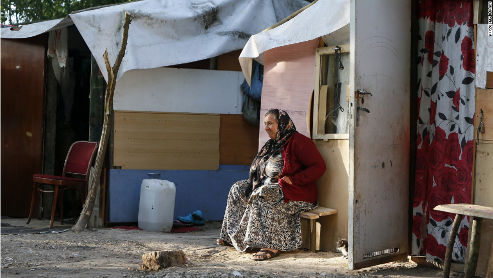 A woman from the Roma community sits in front of a shack.