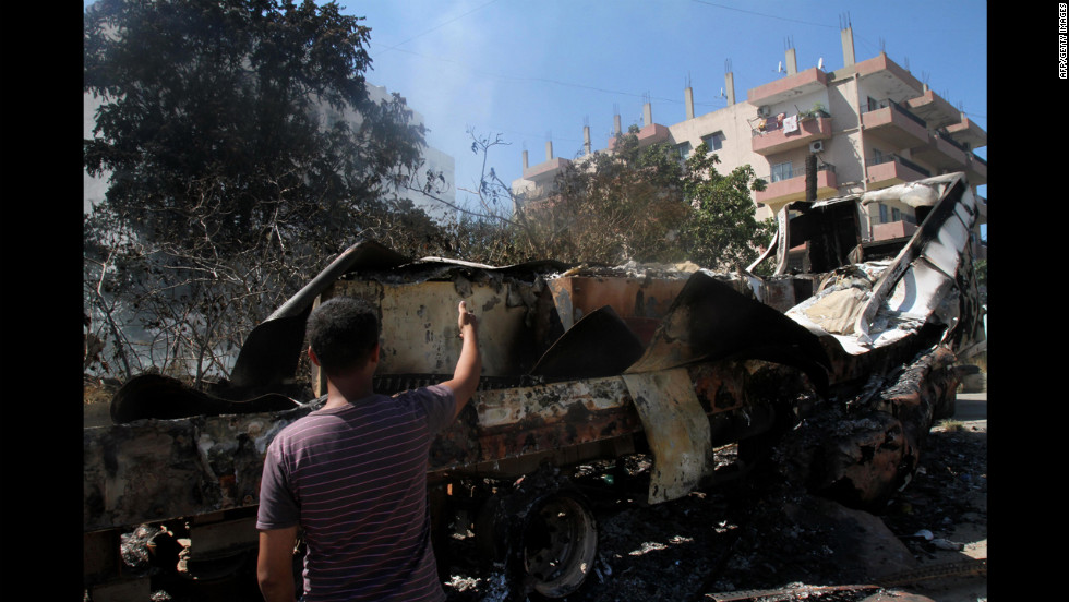 A Lebanese man points at burned vehicles in the Bab al-Tabbaneh neighborhood in Tripoli, Lebanon, on Thursday, August 23. Fresh fighting erupted in Bab al-Tabbaneh, leaving one dead and two wounded, a security source said, despite a truce to halt days of violence between pro- and anti-Damascus gunmen.