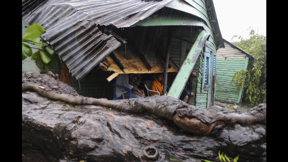 A family looks at a tree brought down by storm winds that hit a corner of their house in El Habanero, Barahona province.