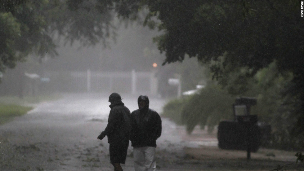People venture out into the stormy weather as Tropical Storm Isaac passed by Marathon, Florida, on Sunday.