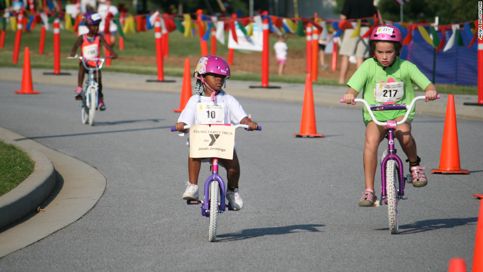 Jonah Jennings, left, rides her new two-wheel bike with pride.