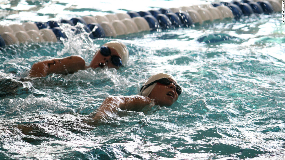 Two senior boys race it out at the end of their 200-yard swim.