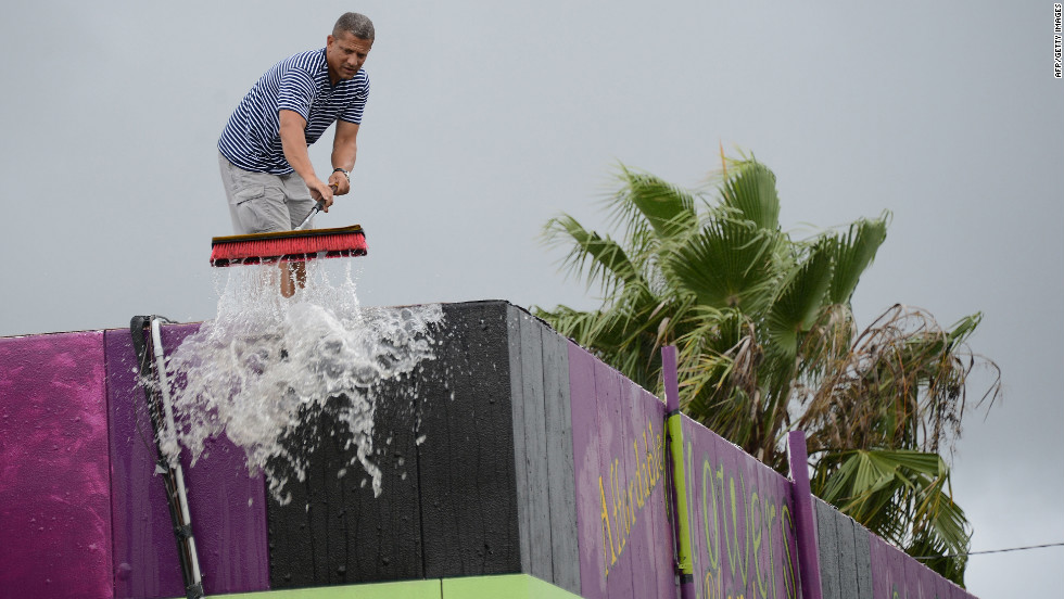 Oliver Marti sweeps water from heavy rains generated by Tropical Storm Isaac off the roof of his flower shop on  Monday in Tampa, Florida.