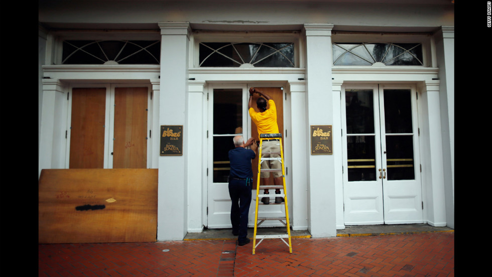 Workers place plywood on the windows of the Royal Sonesta Hotel on Bourbon Street.