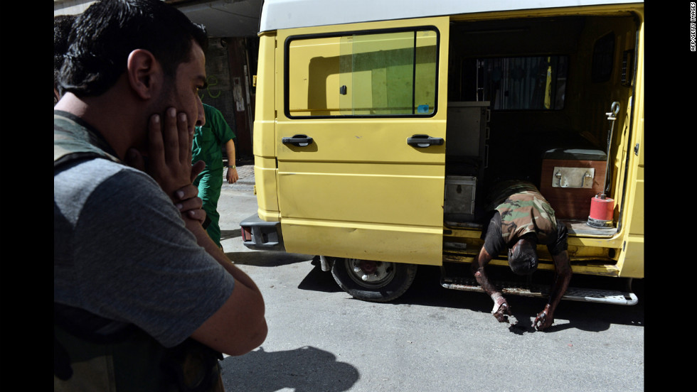 A man reacts as an ambulance arrives with the body of a Free Syrian Army fighter outside a hospital in Aleppo.
