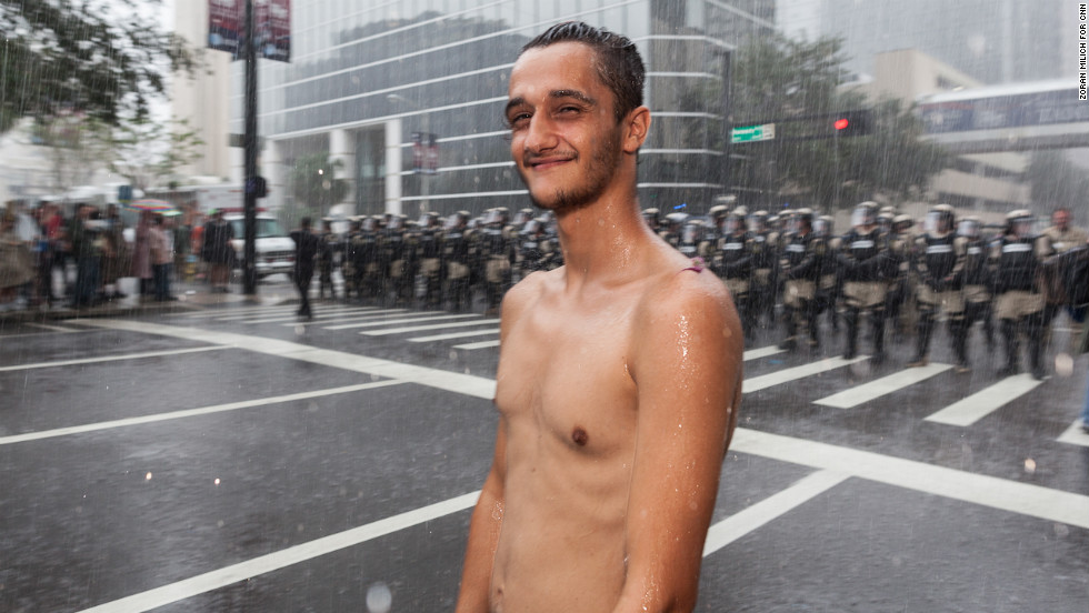 A shirtless protester stands in the rain in front of a police line.