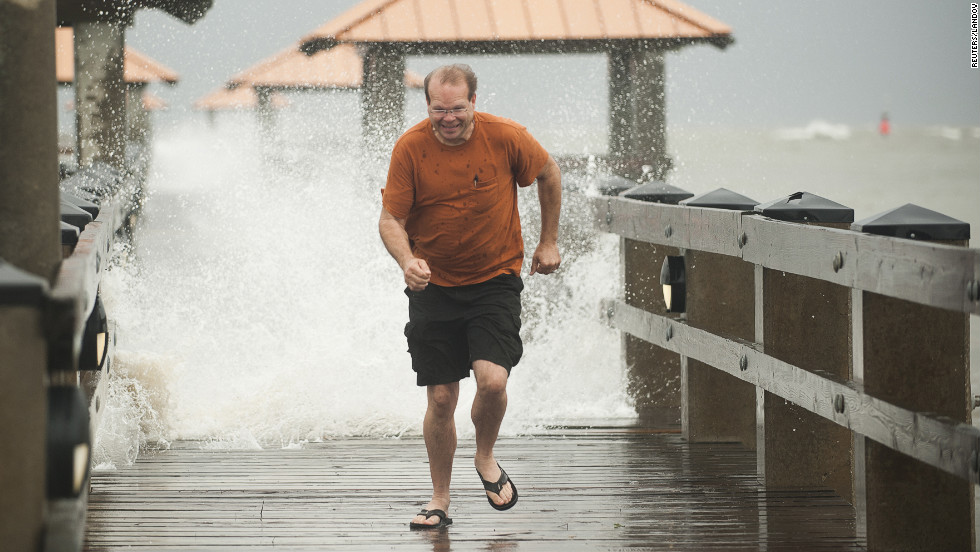 Scott Burley runs from crashing surf on the Ken Combs Pier in Gulfport, Mississippi.