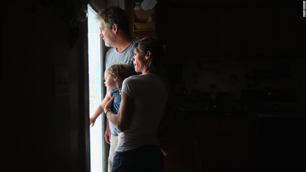 Bridgette Mooney, her husband Kevin, and their 15-month-old daughter Skyler watch from their home as Hurricane Isaac lashes their property with rain in Kiln, Mississippi.