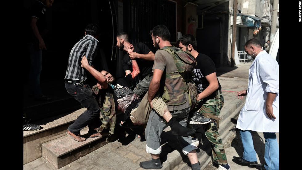 Free Syrian Army fighters carry a wounded member into a hospital in Aleppo on Tuesday, August 28.