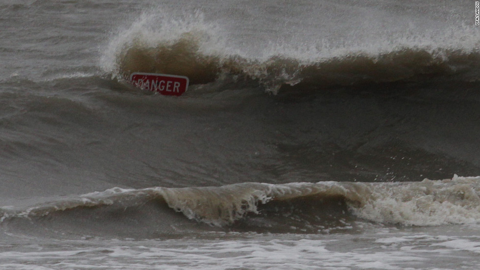 Waves from Hurricane Isaac smash against a warning sign at a flooded beach in Biloxi, Mississippi.