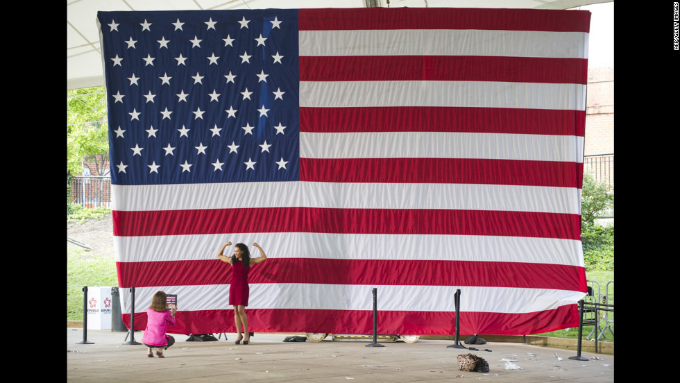 Monica Cabbler poses for photos in front of a U.S. flag after a speech by Obama during a campaign event in Charlottesville, Virginia, on Wednesday, August 29.