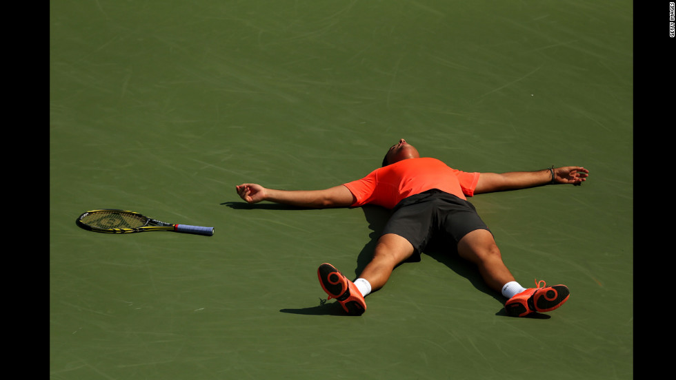 Nicolas Almagro of Spain lies on the court as he celebrates match point after his men's singles second-round match against Philipp Petzschner of Germany.