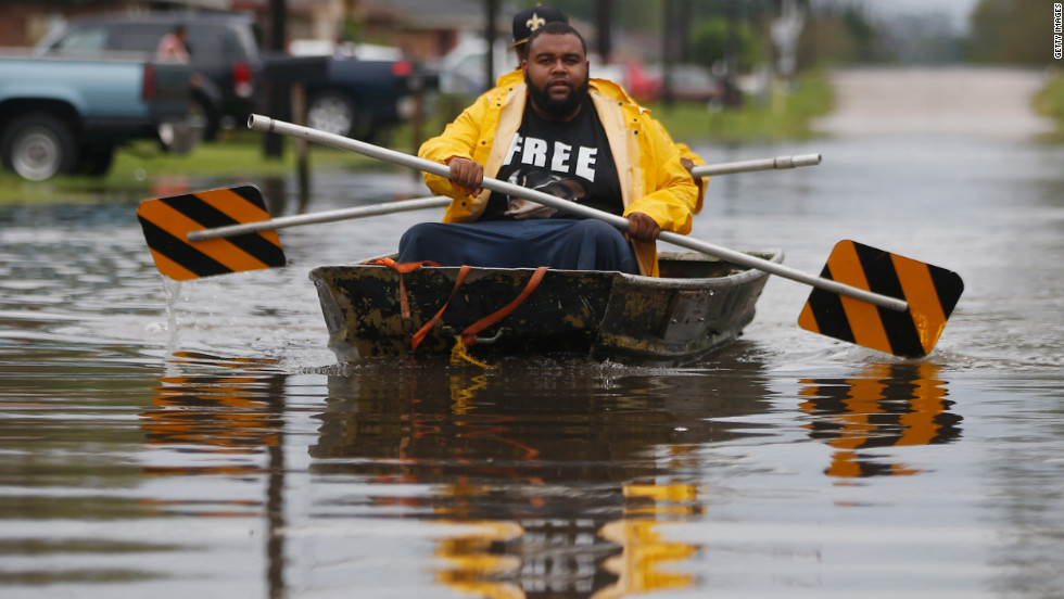 Two men paddle a boat with street signs in flood waters from Hurricane Isaac in Reserve, Louisiana.