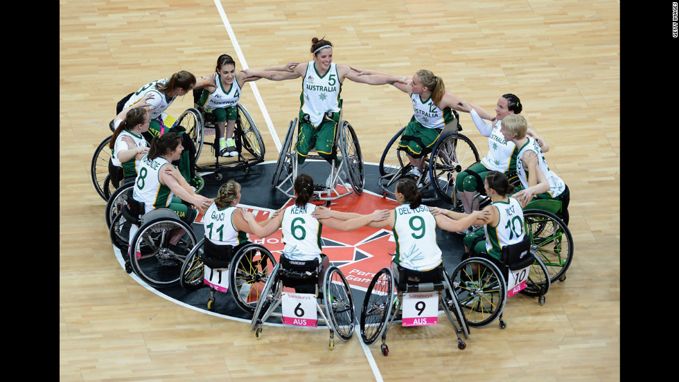 The Australian women's wheelchair basketball team huddles and celebrates their victory during their preliminary basketball game against Brazil.