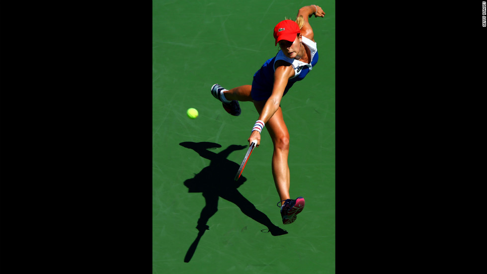 France's Alize Cornet returns a shot during her women's singles second-round match against Czech Petra Kvitova.
