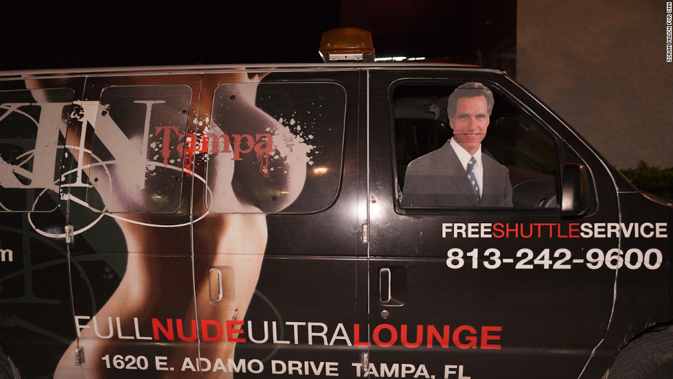 "A Mitt Romney cutout rides in the front seat of a van advertising a ""nude lounge"" during the Republican National Convention on Thursday."