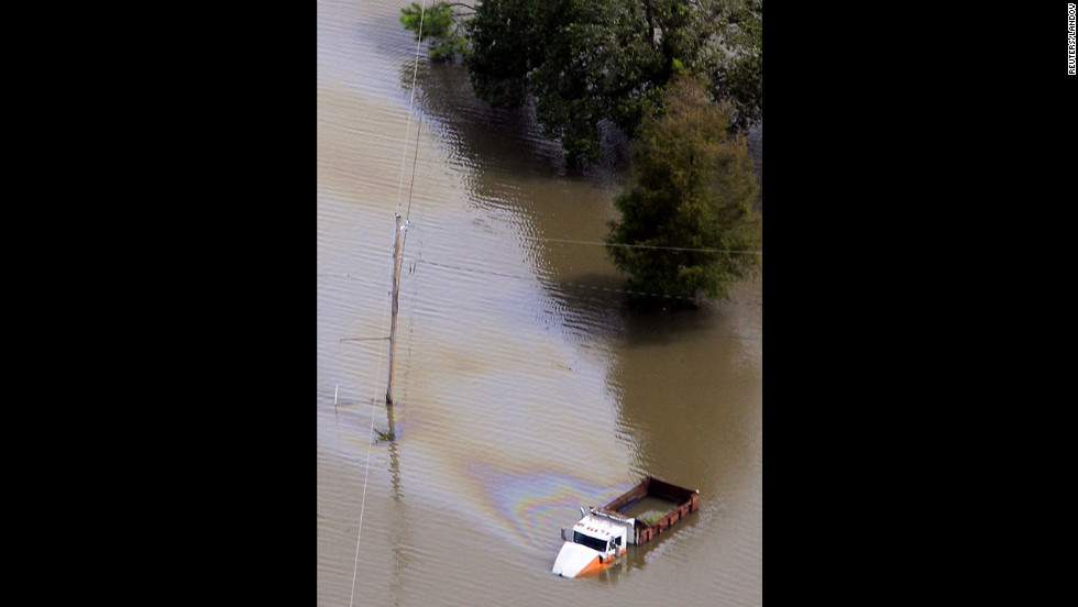 A truck, partially submerged by a levee breach, gives off a sheen of oil and fuel in Braithwaite, Louisiana, on Friday.