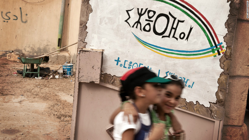 Libyan girls walk past a recently opened Amazigh culture center in Jadu, eastern Libya. The script on the wall is Tifinagh, the Berber alphabet.