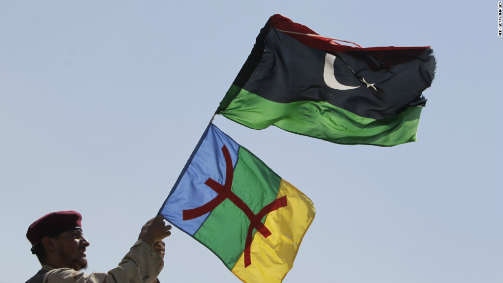 "A soldier waves Libyan and Amazigh flags on the frontline of battle against the remnants of the Gadhafi regime in September 2011. The red symbol on the Amazigh flag is the character for ""free man,"" the name by which Berbers to themselves in Tamazight."