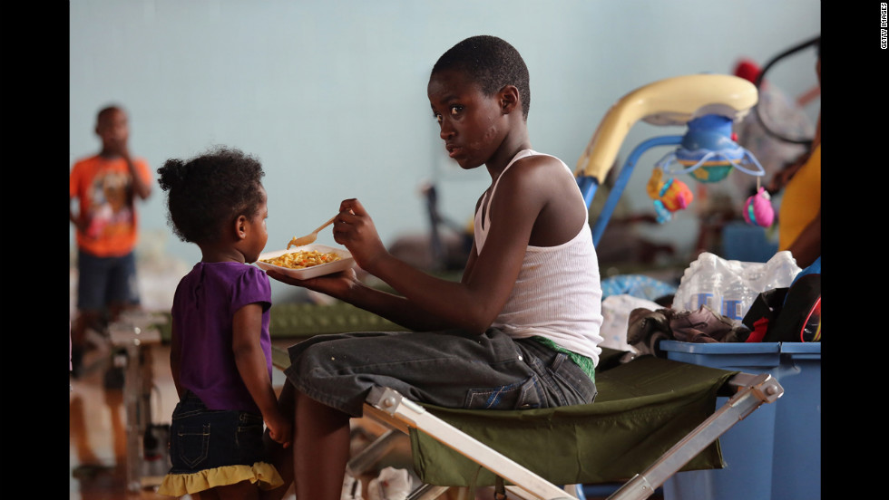 Darrell Hill, 11, feeds his sister Floy Dillon, 2, at a flood shelter set up in a high school gym.