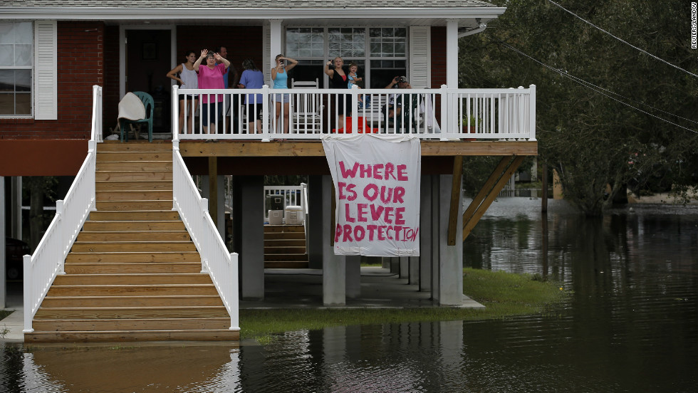 Residents look out from their residence surrounded by water as the motorcade of  Romney passes during a tour of damage from Isaac in Lafitte.