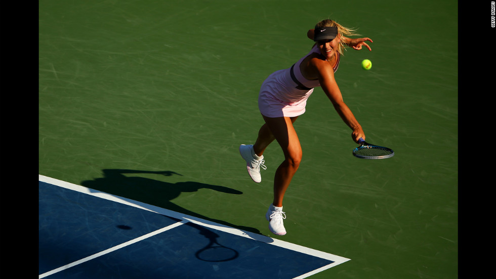 Maria Sharapova of Russia returns a shot against Mallory Burdette of the United States during their women's singles third-round match.