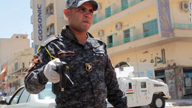 An Iraqi security officer holds a bomb detector device equipped of a silver antenna at a checkpoint in al-Saadun street in central Baghdad.