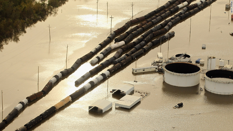 Oil containers and railroad cars sit in Isaac's flood waters in Braithwaite, Louisiana.