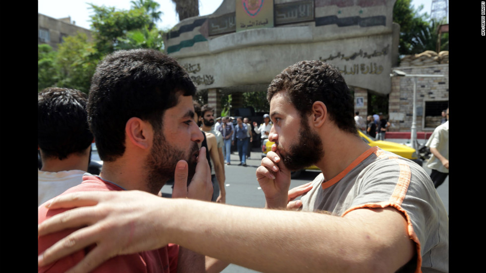 Syrian prisoners congratulate each other as they walk out of the Damascus central police station.