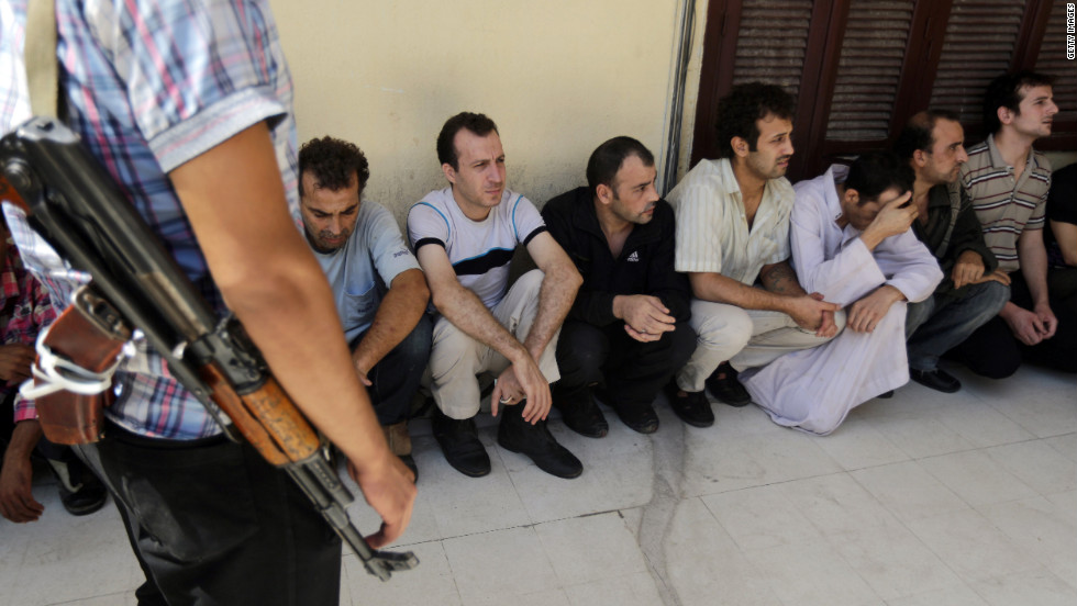 Syrian prisoners wait in line to sign their release papers at the Damascus central police station on Saturday, as the authorities released 158 people from the facility.
